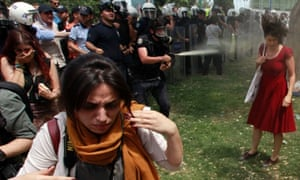 A Turkish riot policeman uses teargas or pepper spray as people protest against the destruction of trees in a park brought about by a pedestrian project, in Taksim Square in central Istanbul on 28 May.