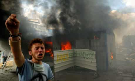 An anti-government protester shouts for help to extinguish a burning container in Taksim Square