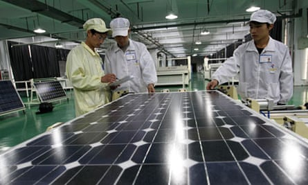 Chinese workers examine solar panels at a plant in Huaibei in China's Anhui province