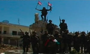 A soldier raises his weapon holding a Syrian flag while standing with fellow soldiers in Qusair after the Syrian army took control of the city from rebel fighters in this still image taken from video. Syrian forces and their Hezbollah militant allies seized control on Wednesday of the border town of Qusair.