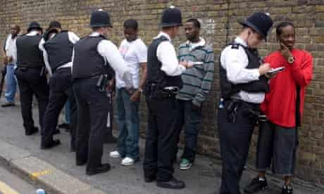 Police stop and search a handful of men near the the Notting Hill Carnival