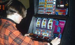 TEENAGE BOY PLAYING A FRUIT MACHINE IN AMUSEMENT ARCADE