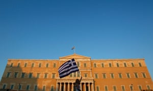 A woman raises a Greek flag during a rally against austerity in front of the parliament at Constitution (Syntagma) square in Athens June 30, 2011.