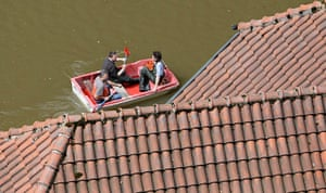 flooding: Local residents paddle their boat past flooded houses in Hrensko