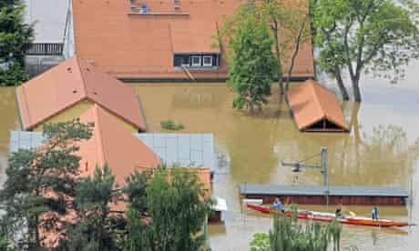 People paddle in a boat between houses flooded by the river Elbe in Dresden