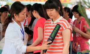A Chinese invigilator scans a student at the gaokao exam in north-east China to prevent cheating
