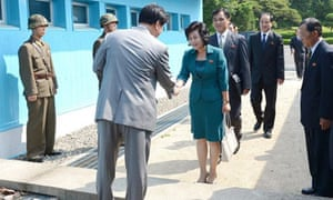 North Korean delegate Kim Song-hye, right, is greeted by a South Korean official in Panmunjom