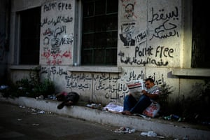 Egypt protest: A protester reads a newspaper during a sit-in protest at Tahrir Square