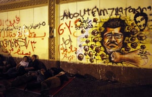 Egypt protest: Egyptian opposition demonstrators sleep next to a wall covered in anti-Mors