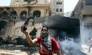 An anti-Morsi protester shows a gun that was allegedly used by Muslim Brotherhood members and seized after storming the headquarters. Reports say at least 12 people were killed in the violence that started yesterday around the Muslim Brotherhood's main offices.