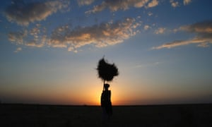 An Afghan silhouetted at sunset carries wheat home on the outskirts of Mazar-e-Sharif. Afghanistan's economy has improved significantly after suffering from decades of fighting, according to latest government reports, boosted by the infusion of international aid and the recovery of the agricultural sector.