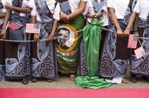 Women wearing khanga traditional wraps with portraits of Barack Obama wait to welcome the US president at an arrival ceremony in Dar es Salaam, Tanzania, for the last leg of his Africa tour