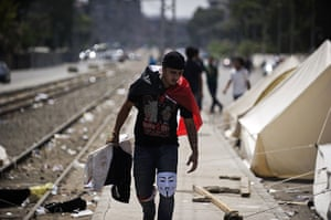 Egypt update: An Egyptian protester with a Guy Fawkes mask on his knee walks past tents s