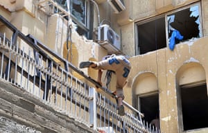 Egypt update: An Egyptian man jumps on the wall at the Muslim Brotherhood's national head