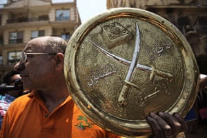 Egypt update: A man holds a plaque of the Muslim Brotherhood emblem which was removed fro