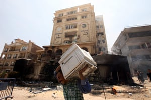 Egypt update: An Egyptian man carries items looted from the headquarters of the Muslim Br