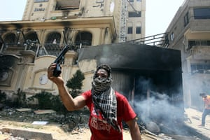 Egypt update: An Egyptian opposing President Morsi shows a gun that was allegedly used by