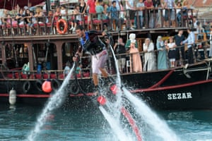 Tourists look on as a man propels himself with water jets at the harbour during an open day in Antalya, Turkey. Antalya is one of the host cities for the FIFA Under 20 World Cup 2013 Soccer Championships.