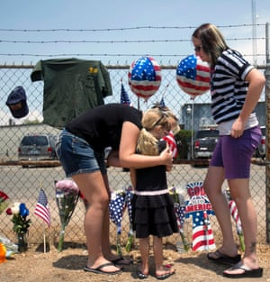 Angela Clark, left, her daughter Chloe, middle, and Theresa Winquest visit a makeshift memorial at the fire station in Prescott, Arizona, where an elite team of firefighters was based. Nineteen of the 20 members of the team were killed when a wildfire suddenly swept toward them in Yarnell, Arizona.