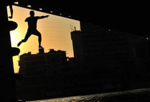 A boy jumps from a pier of bridge against the sunset across Han River in Wuhan, China.