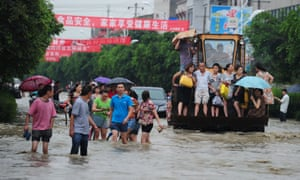 Residents traveling on an excavator as others commute through flooded streets in Chengdu, China.