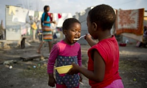 A girl feeds her sister in the shanty town of Nkaneng in South Africa.