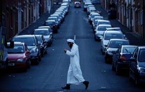 A Muslim man walks to the Masjid e Tauheedul for Maghrit prayers in Blackburn, Lancashire at the start of Ramadan.