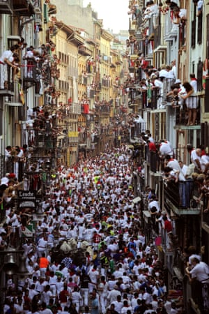 People on balconies watch participants running in front of Victoriano Cortes bulls in Pamploma.