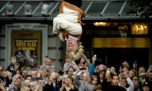 Dutch magician Hans Klok escapes from a strait-jacket while hanging from a crane in front of Carre Theatre in Amsterdam.