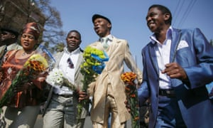 Well-wishers for former South African president Nelson Mandela sing carrying flowers outside the Mediclinic Heart Hospital in Pretoria.