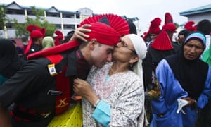 A mother kisses the face of her son after he graduated.