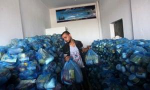 Palestinians receive food aid from a charity in Deir al-Balah, Gaza Strip.