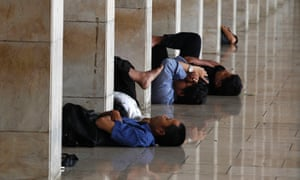 People rest while waiting to break their fast in the Istiqlal mosque during the first day of Ramadan in Jakarta, Indonesia.