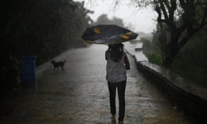 A girl's umbrella is turned upwards by strong winds as she walks during monsoon rains in Mumbai, India.