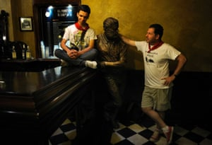 Ernest Hemingway's grandson John, right, and great-grandson Michael stand next to a bust of the author  in Pamplona during the San Fermin festival, which was depicted in Hemingway's 1926 novel The Sun Also Rises.