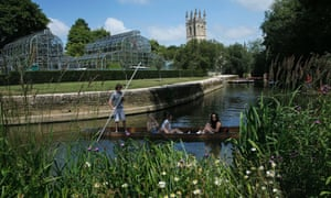 People punt on the river Cherwell past Magdalen College Tower in Oxford.