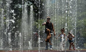 A woman and a dog play in a fountain on a hot day in Tbilisi, Georgia.
