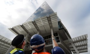 A policeman and emergency services personnel watch as Greenpeace women activists climb the Shard in London. Photograph: Andy Rain/EPA