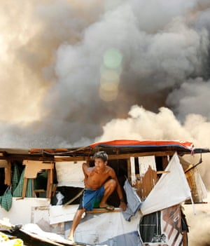A Filipino resident escapes from a burning shanty as a fire engulfs a shanty town in Makati's financial district, Philippines.
