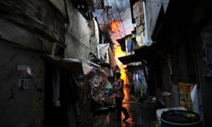 A resident tries to put out a fire after a blaze engulfed a shanty town in Manila.