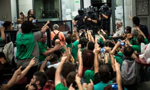 Members of the association for Mortgage Victims' Platform (PAH) face riot police officers before clearing the Banco Popular bank branch in Barcelona, Spain.