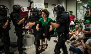 Riot police officers clear the Banco Popular bank after being occupied by activists. Photograph: David Ramos/Getty Images