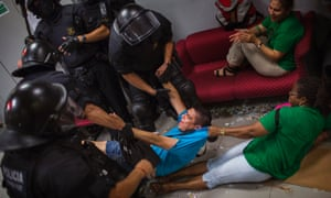 Activists are dragged by riot police officers after occupying the bank as part of a protest to support a neighbour who is facing an eviction process.