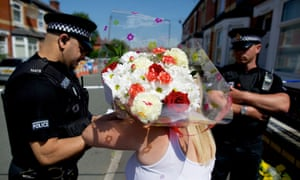A woman arrives to place flowers at the scene in Gorton, east Manchester, where a 23 year old man was tasered by police officers after a disturbance yesterday evening. The man later suffered a 'medical episode' and died in hospital. Read the latest report.