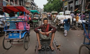 An Indian laborer rests on his handcart, placed as a road divider, at a wholesale market in New Delhi. The photograph is one of a series documenting daily life in the city.