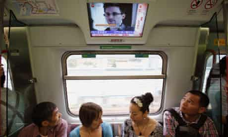 Passengers on a train in Hong Kong watch a TV showing news on Edward Snowden, the US whistleblower.