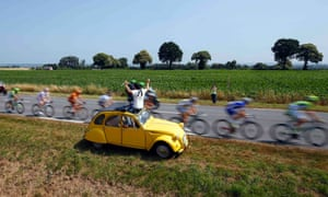 A spectator in a yellow Citroen 2CV car waves as the pack of riders cycles on its way during the twelfth stage of the Tour de France cycling race from Fougeres to Tours. A delightful visual cliche!