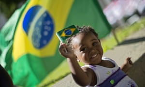 A child belonging to a stallholder selling Brazilian national flags plays at Canderia Square in Rio de Janeiro where the unions rally will take place later today.