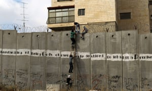 Palestinians use a ladder to climb over the separation barrier in Ar-Ram, north of Jerusalem, on their way to the al-Aqsa mosque in the Old City of Jerusalem to attend the first Friday prayer in the fasting month of Ramadan.