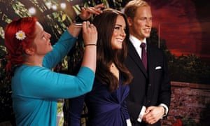 Wardrobe supervisor Jane Anderson makes final adjustments to wax figures of the Duke and Duchess of Cambridge at Madame Tussauds, London, after they were moved to a summer garden setting at the venue.